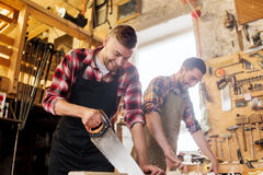 Carpenters working with saw and wood at workshop Royalty Free Stock Photography