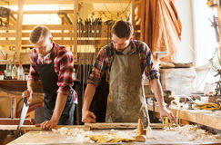 Carpenters working with saw and wood at workshop Stock Image