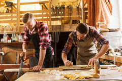 Carpenters working with saw and wood at workshop Royalty Free Stock Photos
