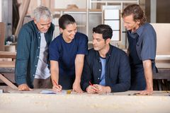 Carpenters Working Together On Blueprint Royalty Free Stock Photo