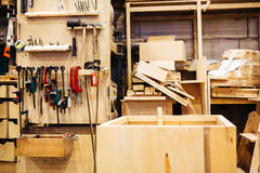 Carpenters Workshop. Background image of empty carpenters workshop: various woodworking tools, wooden boards and parts of furniture in factory Stock Image