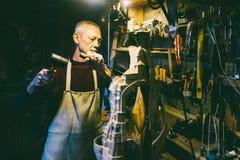 Carpentiere 50 - 55 anni crea la scultura di legno nell'officina fotografia stock libera da diritti
