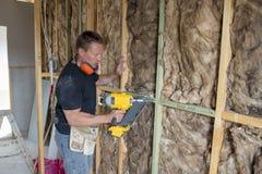 Carpentiere attraente e sicuro del costruttore o legno di lavoro dell'uomo del costruttore con il trapano elettrico al cantiere i Fotografia Stock