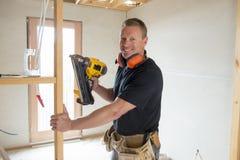 Carpentiere attraente e sicuro del costruttore o legno di lavoro dell'uomo del costruttore con il trapano elettrico al cantiere i immagini stock