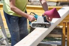 Carpentiere che ammorbidisce i bordi sui fasci della costruzione fotografia stock