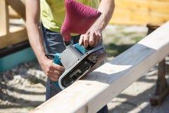 Carpentiere che ammorbidisce i bordi sui fasci della costruzione immagini stock libere da diritti