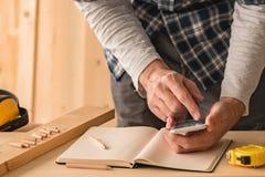 Carpentiere che effettua calcolo di progetto facendo uso del app dello smartphone fotografia stock libera da diritti