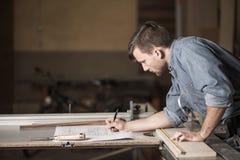 Carpentiere che esamina i piani Immagine Stock