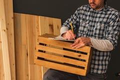 Carpentiere che fa cassa di legno nell'officina della lavorazione del legno di piccola impresa immagini stock