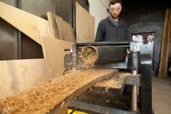 Carpentiere che fa funzionare la piallatrice fissa di potere, elaborante p di legno immagini stock