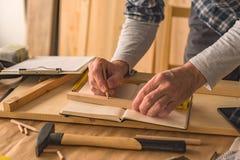 Carpentiere che fa la cornice in officina fotografia stock