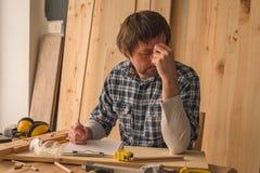 Carpentiere che fa le note di progetto della lavorazione del legno sulla carta della lavagna per appunti fotografia stock