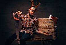 Carpentiere che indossa il cappuccio decorato di natale che si siede su una tavolozza di legno fotografia stock