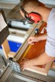 Carpentiere che lavora alle macchine per la lavorazione del legno nel negozio di carpenteria immagini stock