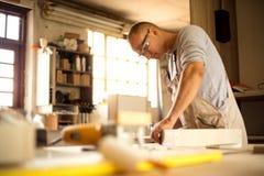 Carpentiere che lavora alle macchine per la lavorazione del legno nel negozio di carpenteria fotografia stock