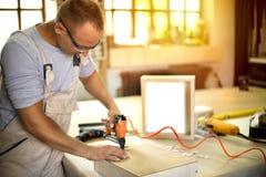 Carpentiere che lavora alle macchine per la lavorazione del legno nel negozio di carpenteria immagine stock