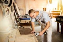Carpentiere che lavora alle macchine per la lavorazione del legno nel negozio di carpenteria fotografia stock libera da diritti