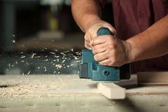 Carpentiere che lavora con la piallatrice elettrica Fotografia Stock