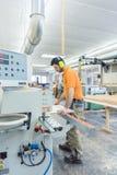 Carpentiere che lavora nella fabbrica della mobilia sulla macchina immagine stock