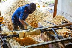 Carpentiere che lavora un pezzo al tornio di legno usando la macchina del tornio per fare Immagine Stock Libera da Diritti