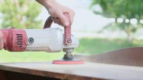 Carpentiere che lucida una tavola di legno con una sabbiatrice elettrica in primo piano dell'officina video d archivio
