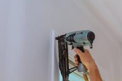 Carpentiere che per mezzo della pistola ai modanature sulle finestre, disposizione d'inquadramento del chiodo, Fotografia Stock Libera da Diritti
