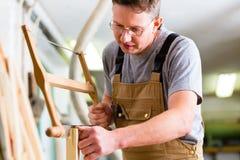 Carpentiere che per mezzo della sega della mano Fotografie Stock