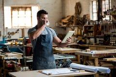 carpentiere che per mezzo della sua compressa e bevendo un caffè immagini stock libere da diritti