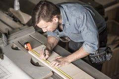 Carpentiere che per mezzo di un nastro di misurazione Fotografia Stock Libera da Diritti