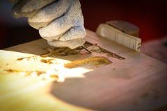 Carpentiere che scolpisce legno con uno scalpello Immagini Stock Libere da Diritti