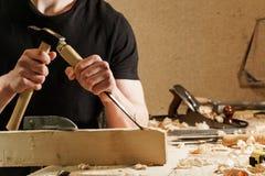 Carpentiere che scolpisce legno con uno scalpello immagine stock