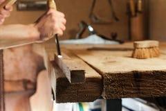 Carpentiere che scolpisce legno con uno scalpello immagine stock libera da diritti