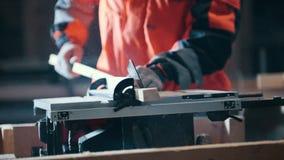 Carpentiere che taglia plancia di legno con la sega elettrica circolare pericolosa video d archivio