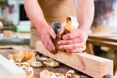 Carpentiere con la piallatrice ed il pezzo in lavorazione di legno in carpenteria Immagine Stock Libera da Diritti