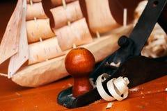 Carpentiere di legno con un aereo, chip, corteccia dell'officina del giocattolo della nave di betulla, casalinga Fotografie Stock
