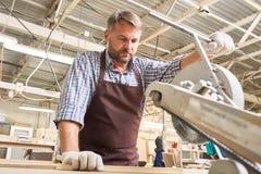 In carpentiere esperto Cutting Wood in falegnameria immagini stock