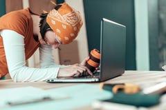Carpentiere femminile sorridente felice durante la chiacchierata online immagini stock
