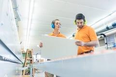 Carpentiere nella fabbrica della mobilia che ispeziona pezzo nel QA immagini stock
