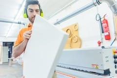 Carpentiere nella fabbrica della mobilia che lavora alla macchina dell'impiallacciatura Fotografie Stock Libere da Diritti