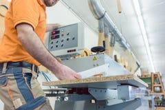 Carpentiere nella fabbrica della mobilia che preme bottone sulla macchina immagine stock