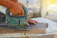 Carpentiere o falegname che lavora con la sega elettrica - primo piano sulle mani, carpentiere sulla natura, carpentiere in Taila Immagine Stock