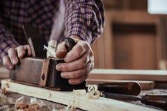 Carpentiere o falegname che spiana una plancia di legno immagini stock libere da diritti