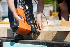 Carpentiere professionista che per mezzo della pistola pneumatica del chiodo immagini stock