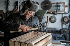 Carpentiere senior anziano in vestiti caldi grigi in occhiali immagine stock