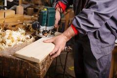 Carpentiere sul lavoro con falegnameria elettrica della piallatrice Fotografie Stock Libere da Diritti