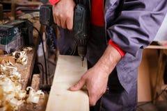 Carpentiere sul lavoro con un trapano in falegnameria Fotografia Stock