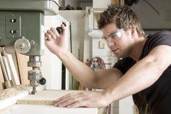 Carpentiere sul lavoro sul lavoro facendo uso della macchina utensile Immagini Stock Libere da Diritti