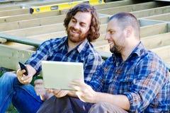 Carpentieri che confrontano le note dal telefono e dalla compressa Fotografie Stock