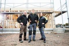 Carpentieri che stanno con le mani sulle anche al cantiere Immagini Stock Libere da Diritti