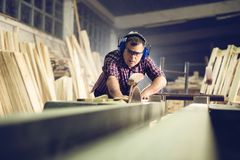 Carpentieri che tagliano plancia di legno con una sega circolare fotografie stock libere da diritti